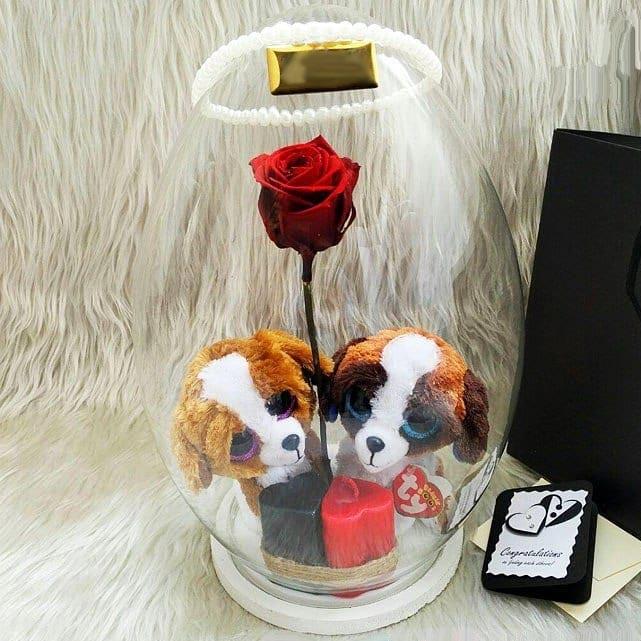سبد شیشه ای با یک گل رز و دو عروسک سگ